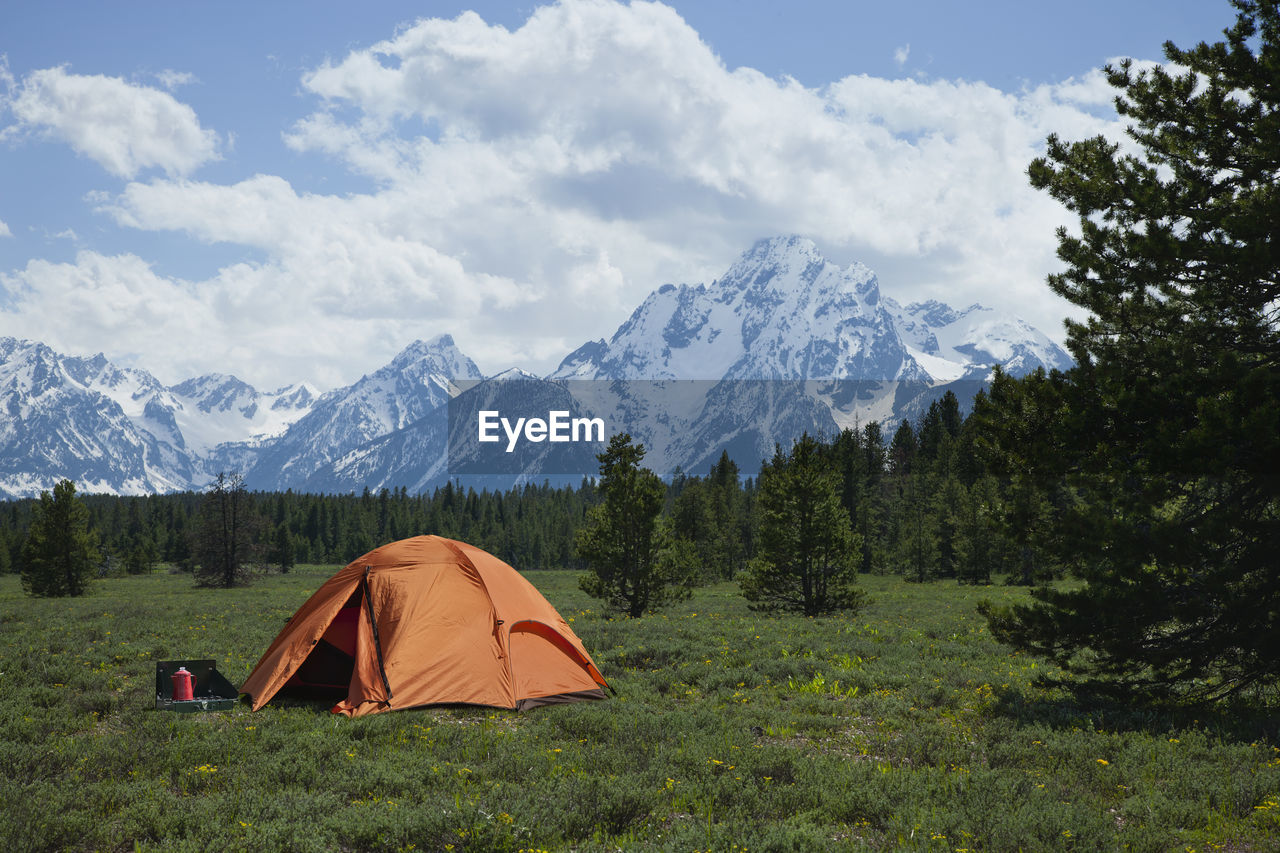 Tent On Grassy Field Against Snowcapped Mountains During Winter