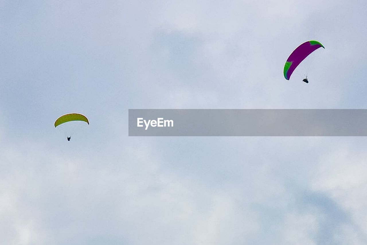 adventure, extreme sports, sport, flying, sky, parachute, paragliding, unrecognizable person, leisure activity, mid-air, low angle view, cloud - sky, real people, gliding, lifestyles, nature, freedom, day, transportation, joy, outdoors, parasailing