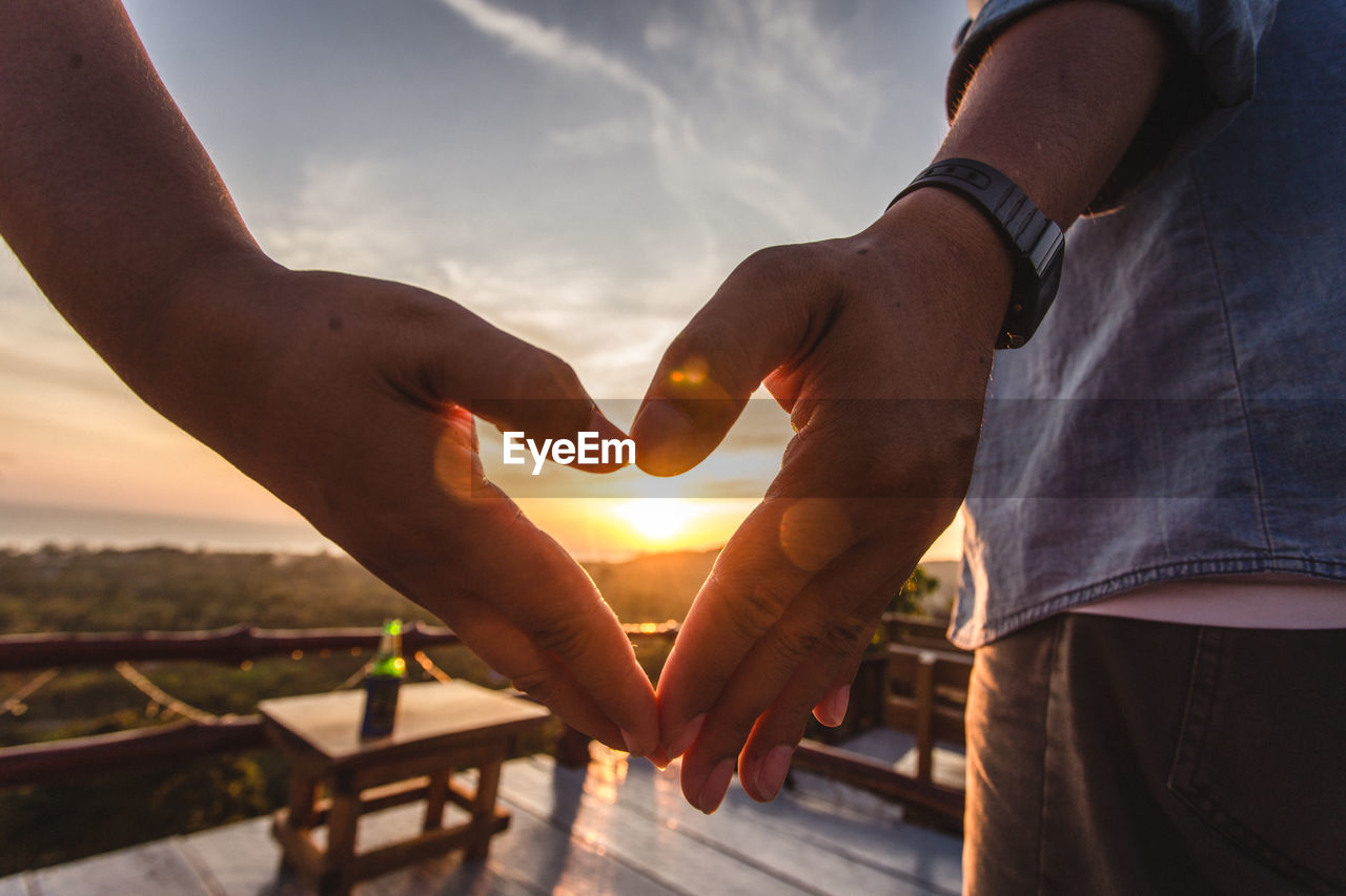 Close-Up Of Hands Shaping Heart During Sunset