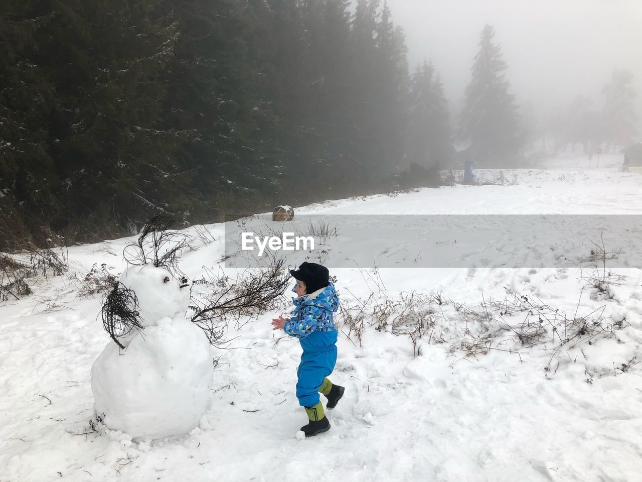 cold temperature, snow, winter, full length, real people, warm clothing, white color, nature, leisure activity, child, one person, day, childhood, beauty in nature, tree, clothing, lifestyles, land, covering, outdoors, extreme weather, innocence