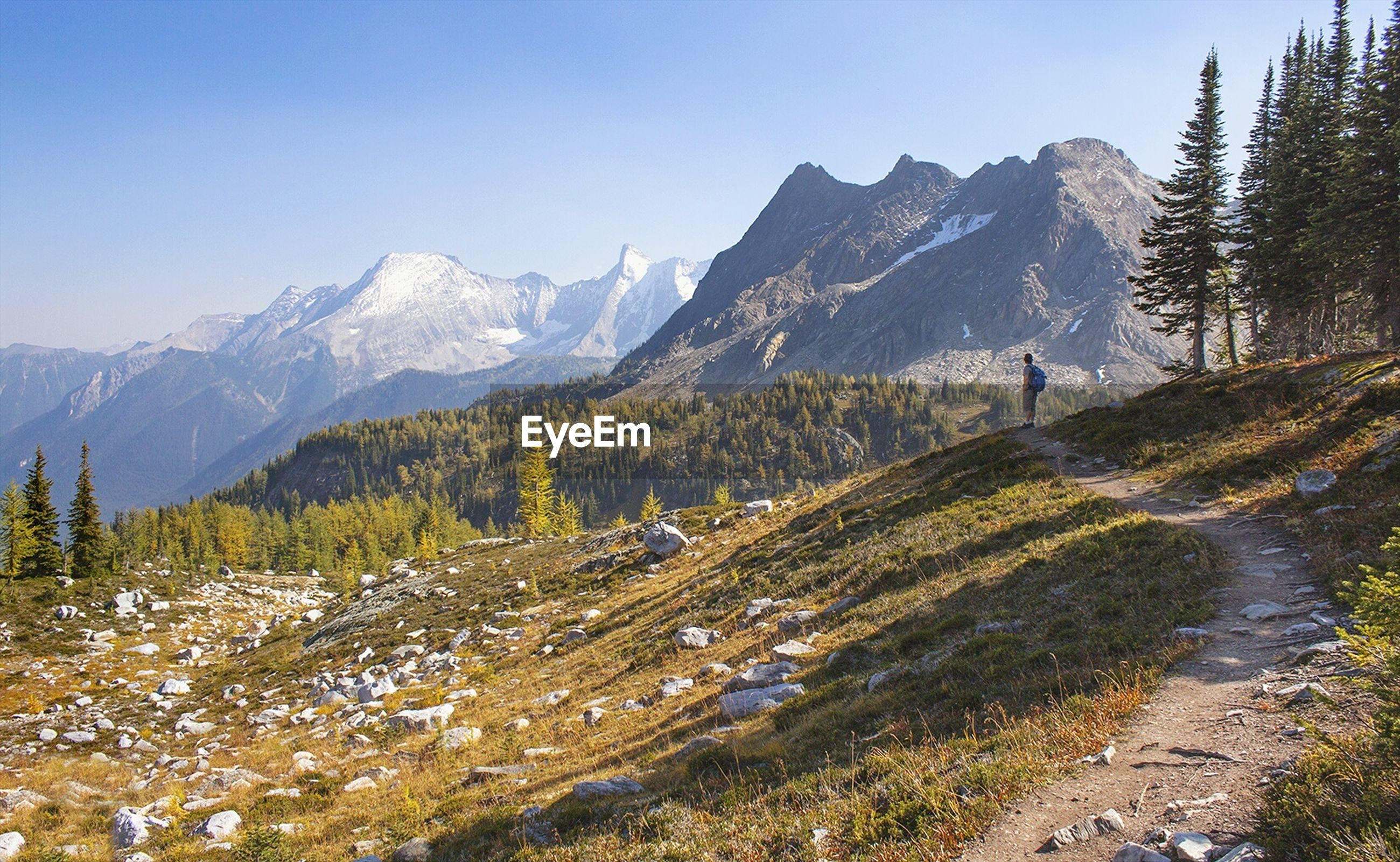 Man hiking by mountains against clear sky