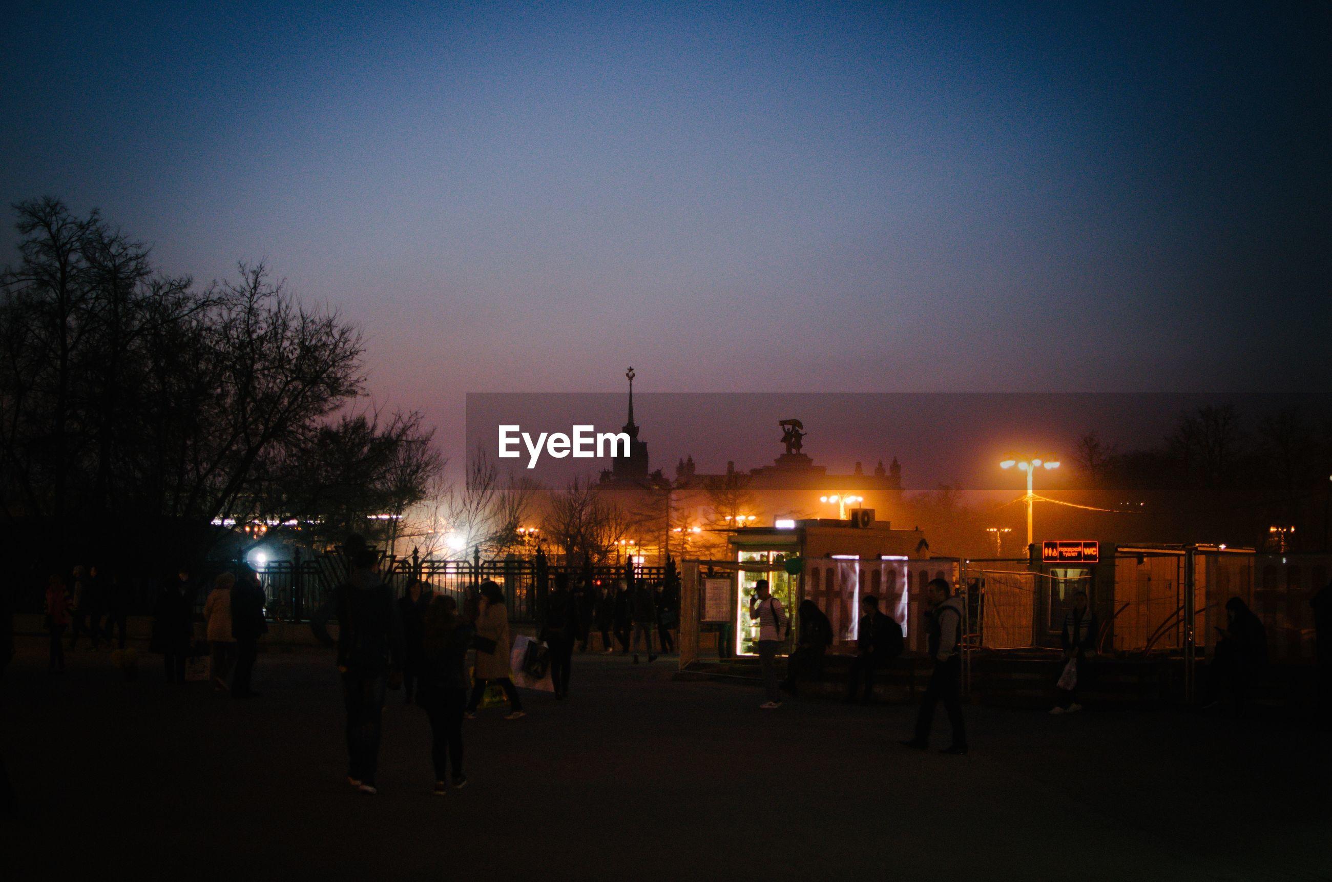 SILHOUETTE OF PEOPLE ON ILLUMINATED STREET AT NIGHT