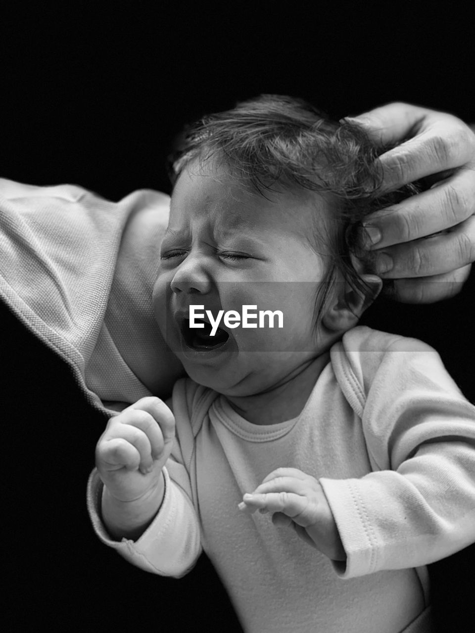 Cropped Hand Touching Crying Toddler Girl Against Black Background
