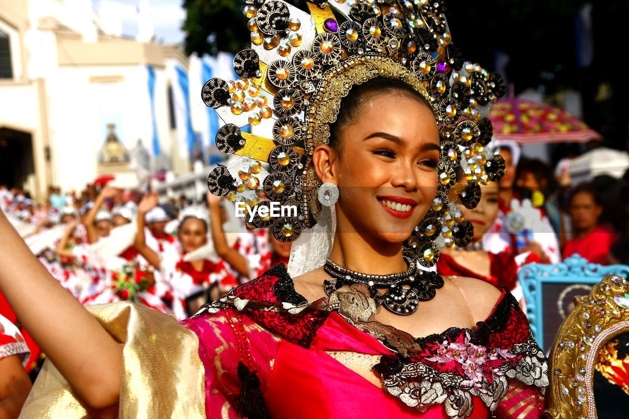 smiling, celebration, real people, focus on foreground, traditional clothing, happiness, women, portrait, lifestyles, young adult, adult, people, headshot, young women, event, clothing, costume, incidental people, traditional dancing, beautiful woman, festival