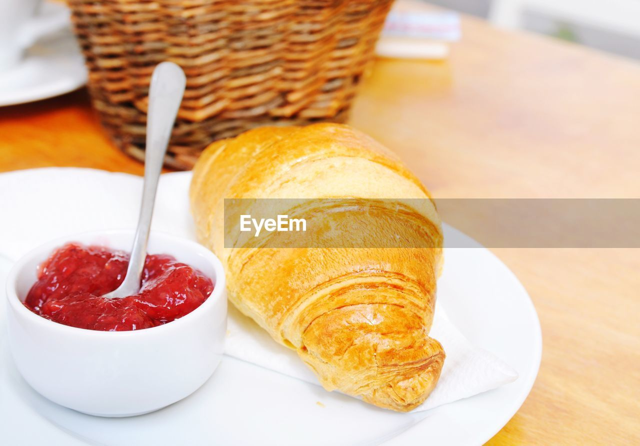Close-Up Of Croissant And Jam In Plate On Table