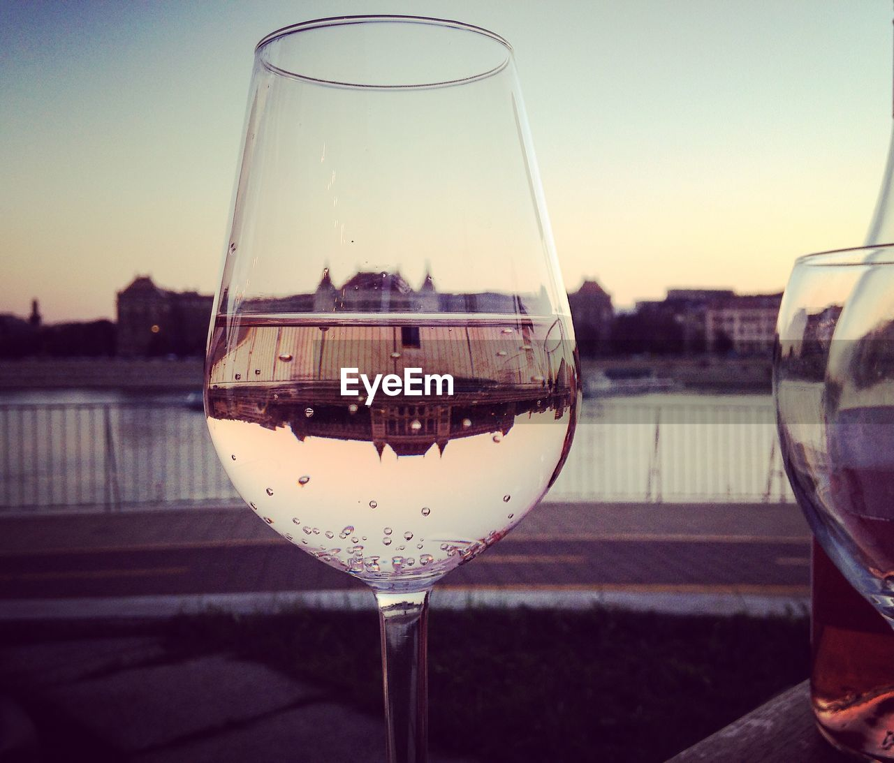 Close-up of wine glass against the lake