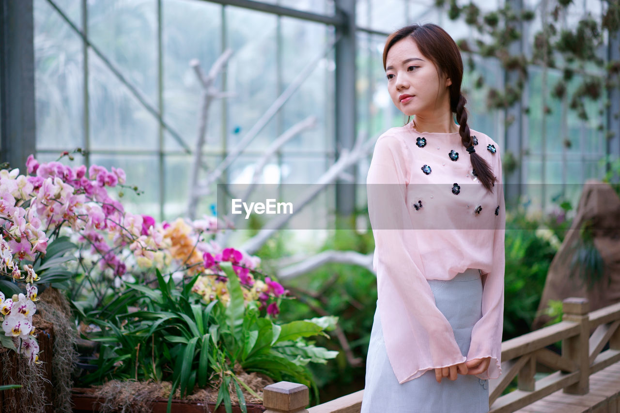 Thoughtful Young Woman Standing By Flowers In Greenhouse