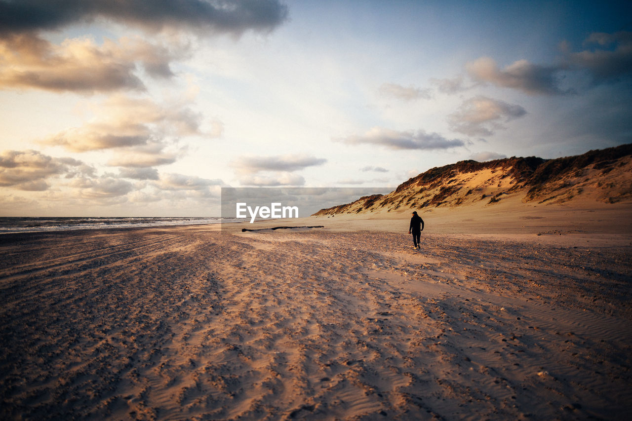 Person walking on sand against sea at beach