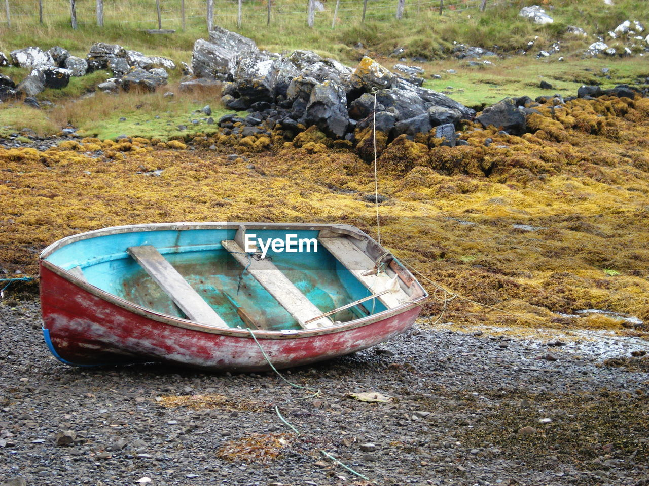 nautical vessel, land, transportation, nature, day, mode of transportation, water, abandoned, moored, no people, rock, rock - object, beach, outdoors, solid, rowboat, lake, high angle view