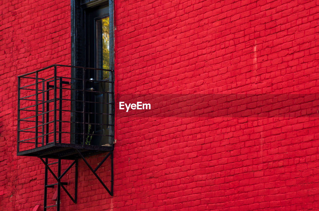 built structure, architecture, building exterior, red, wall - building feature, brick, wall, no people, brick wall, building, window, day, outdoors, low angle view, residential district, metal, pink color, pipe - tube, safety, nature