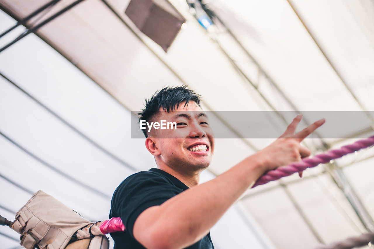 one person, real people, men, portrait, lifestyles, headshot, looking, low angle view, indoors, standing, leisure activity, front view, selective focus, smiling, casual clothing, happiness, young men, males, ceiling