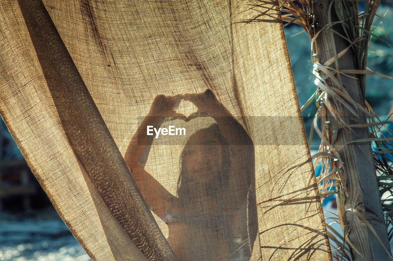Close-Up Girl Behind Curtain On Beach