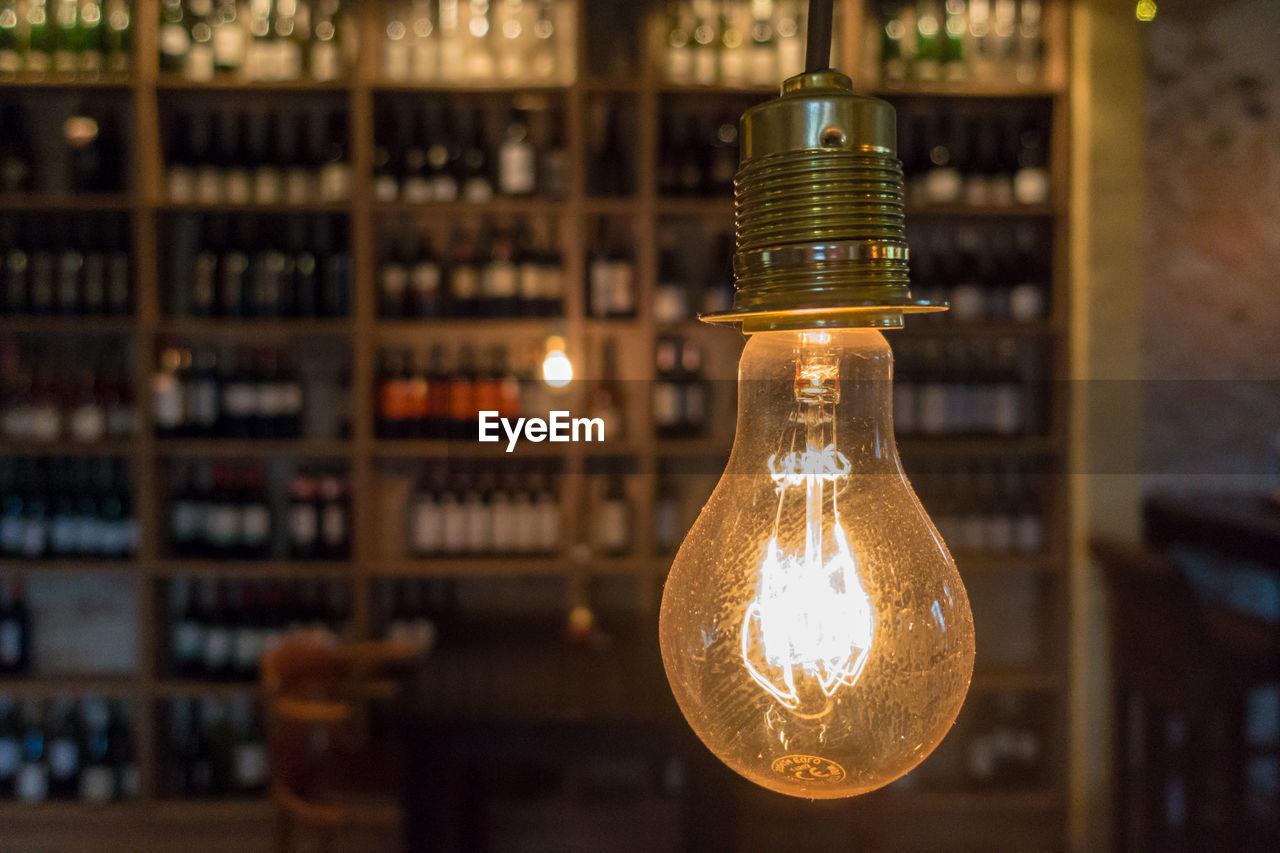 Close-Up Of Illuminated Light Bulb In Bar