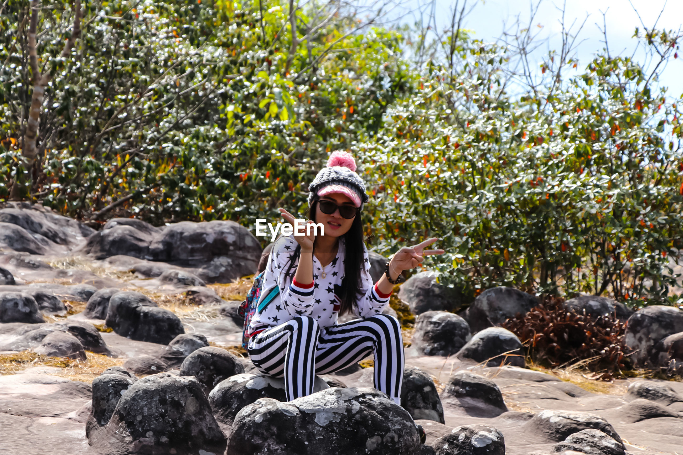 Young woman showing peace sign while sitting on stone