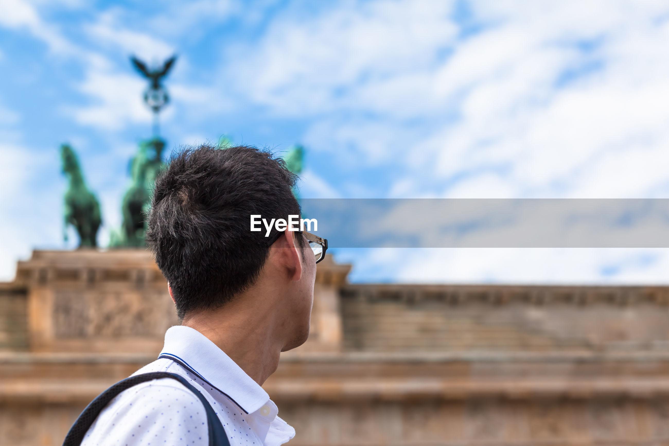 Side view of man looking away against sky in city