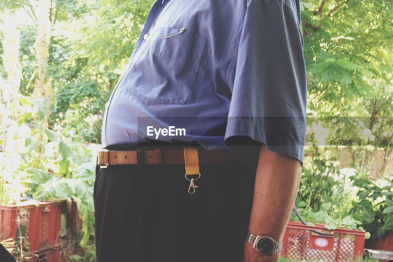 midsection, real people, day, lifestyles, women, people, standing, adult, focus on foreground, leisure activity, rear view, human body part, outdoors, clothing, nature, casual clothing, fashion, men, plant