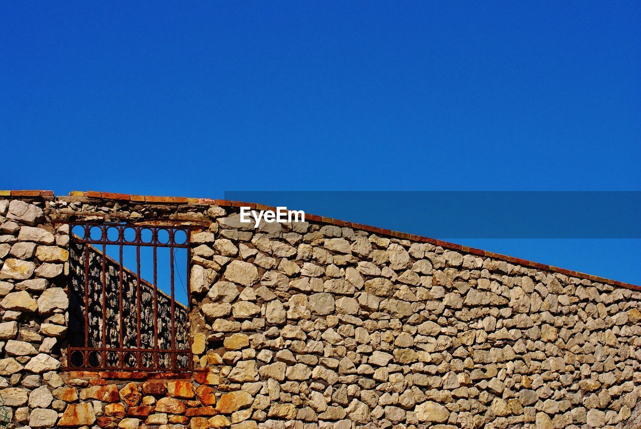 Low angle view of old stone wall against clear blue sky during sunny day