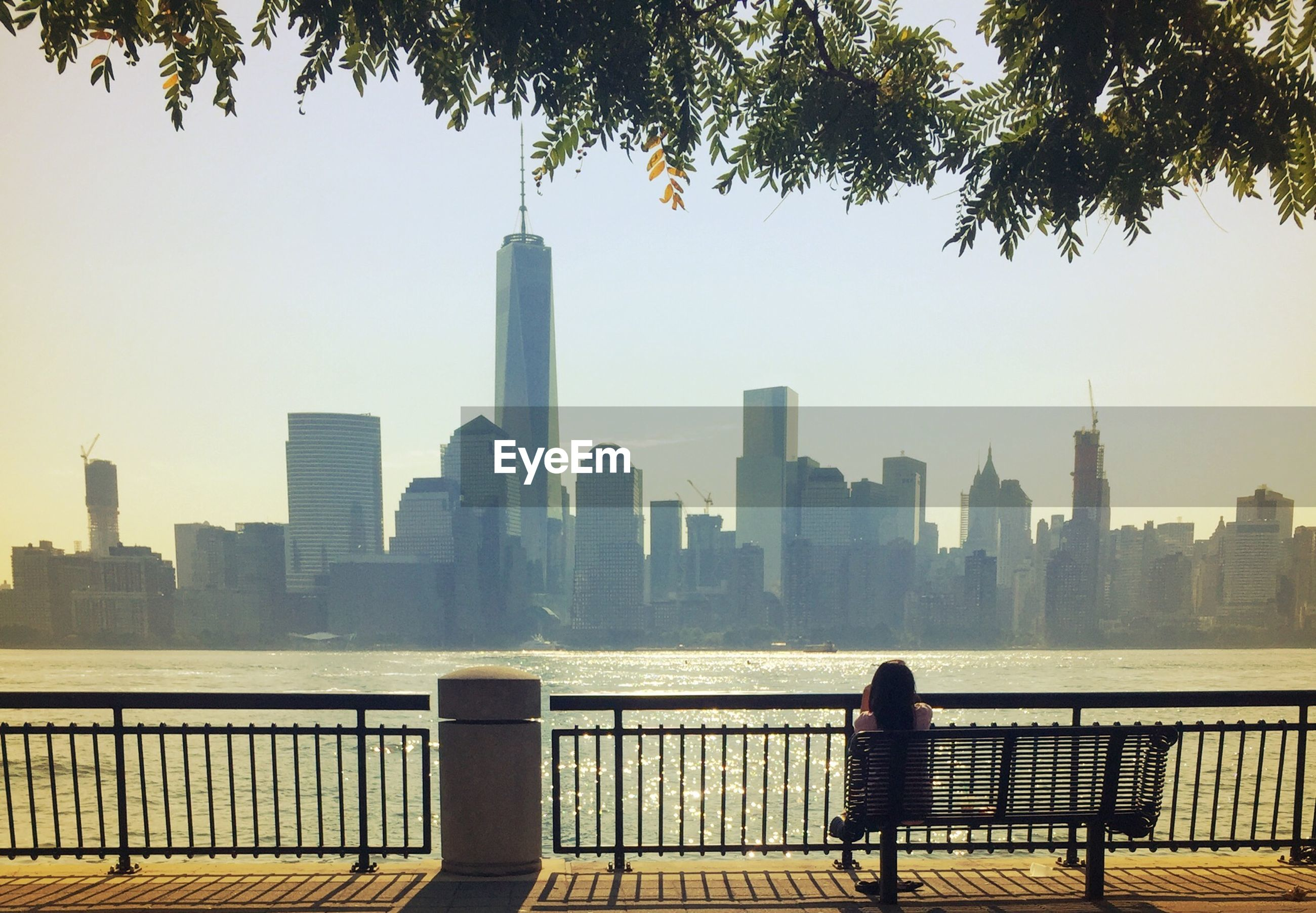 Rear view of woman sitting on bench looking at one world trade center in cityscape
