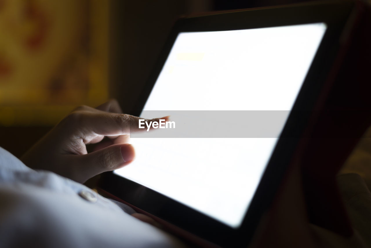 Midsection Of Person Using Digital Tablet In Darkroom