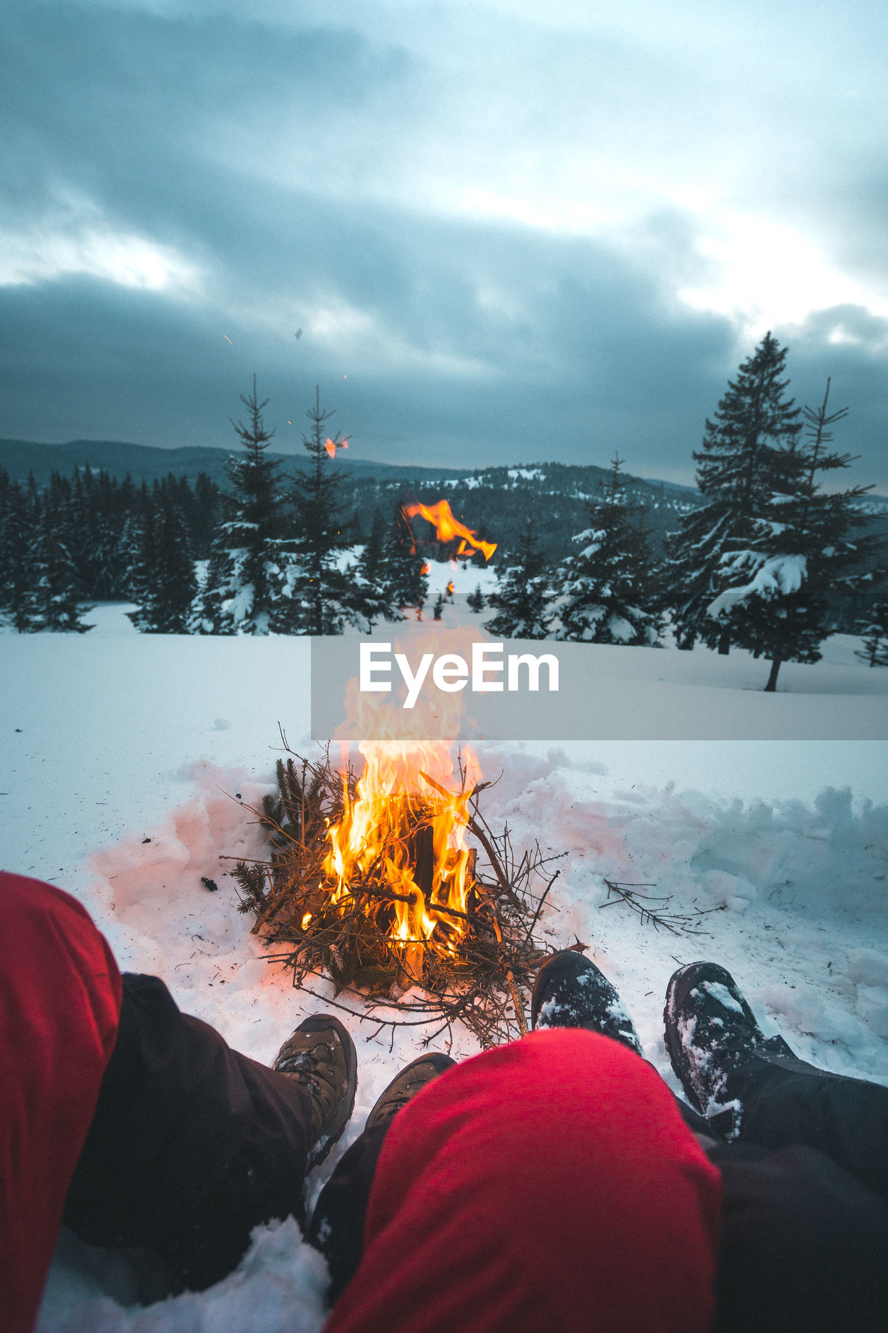 Low section of couple on snow covered land by fire