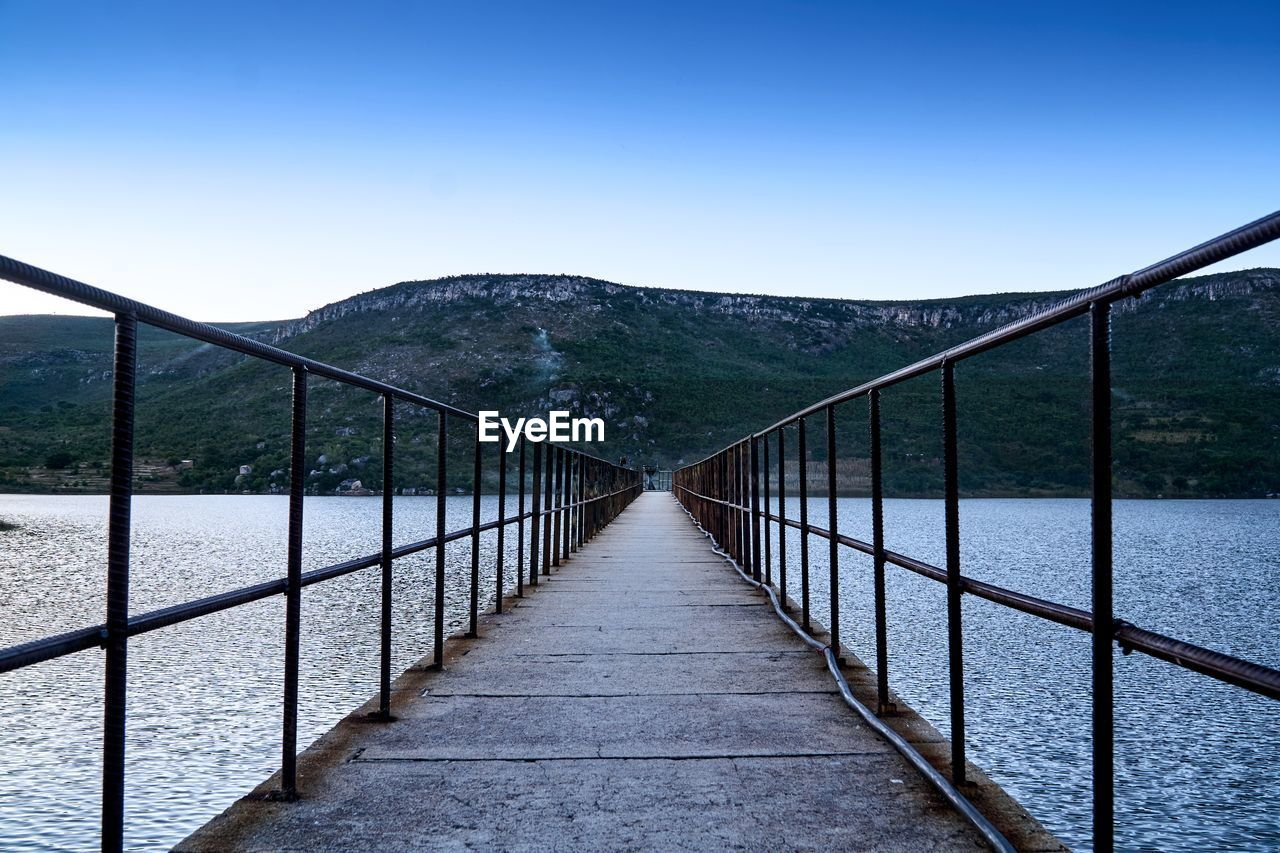 mountain, railing, the way forward, tranquil scene, scenics - nature, tranquility, sky, direction, nature, clear sky, day, no people, non-urban scene, beauty in nature, connection, water, bridge, idyllic, tree, footbridge, diminishing perspective, bridge - man made structure, outdoors