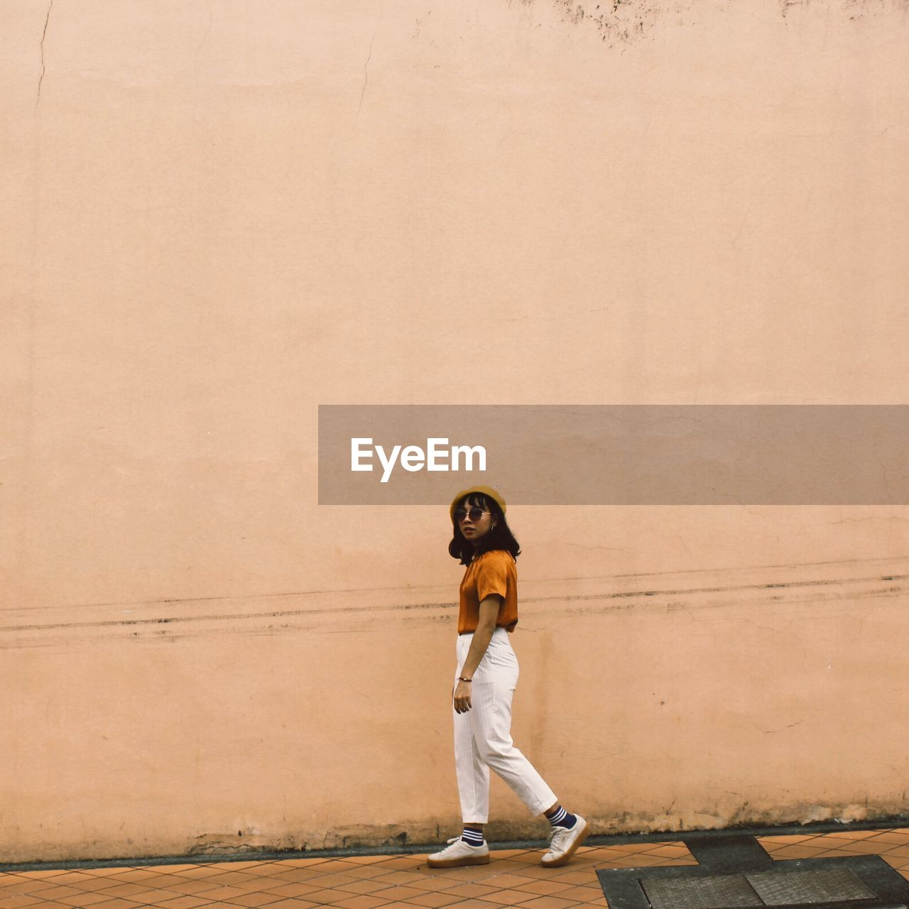 Full length of young woman walking on sidewalk by wall