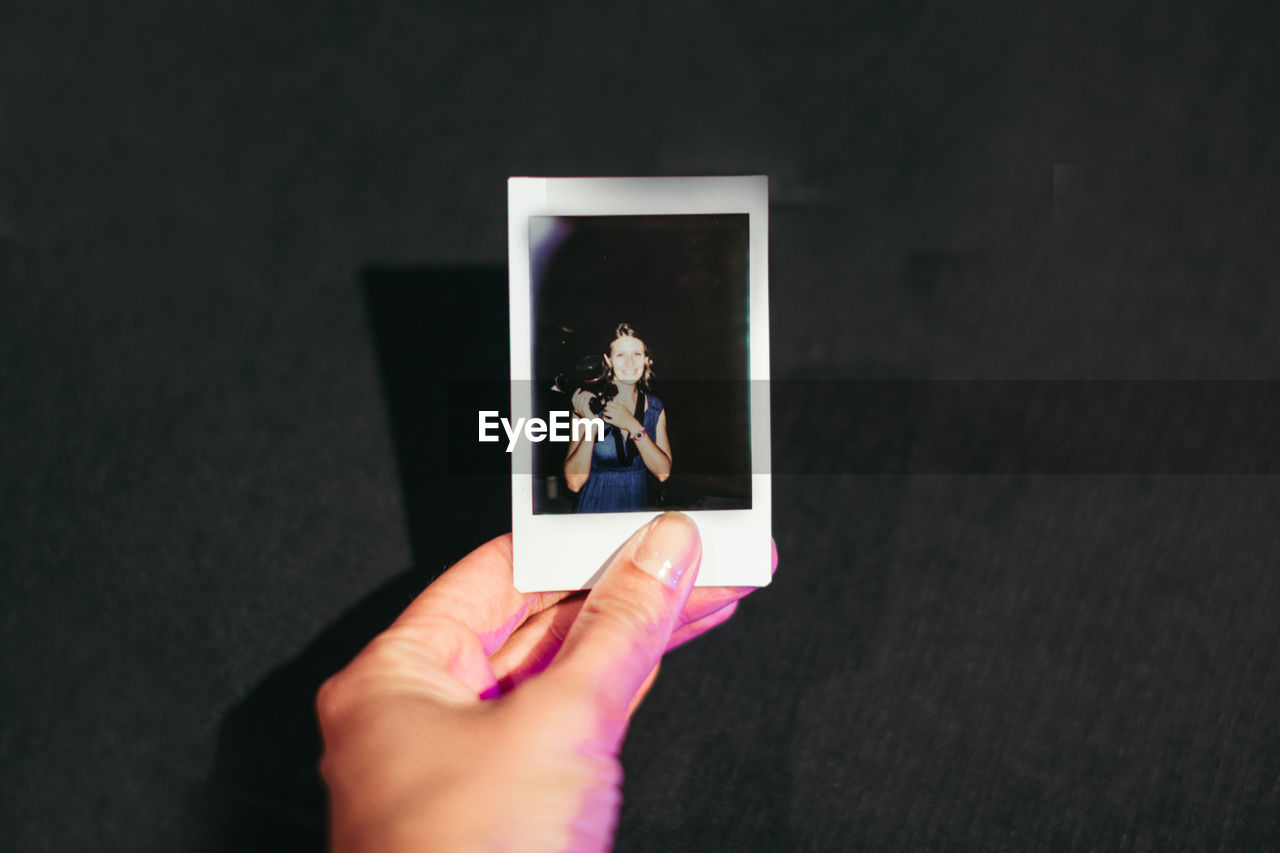 Cropped Image Of Photographer Holding Picture Frame Over Table