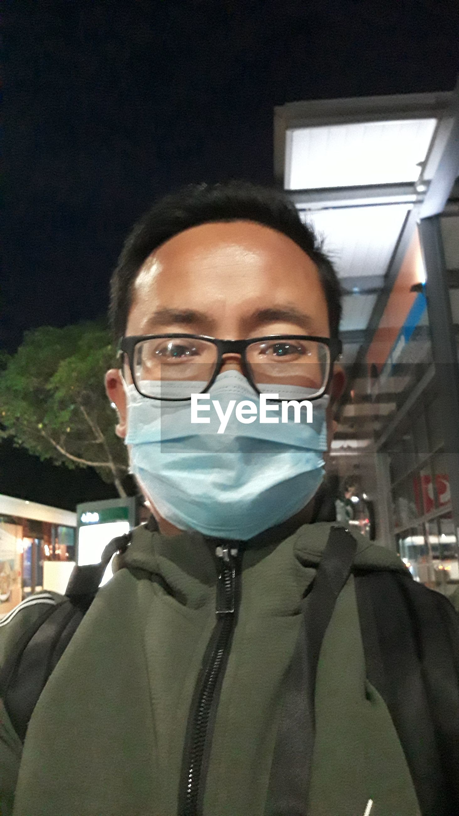 Portrait of man with eyeglasses wearing mask in city