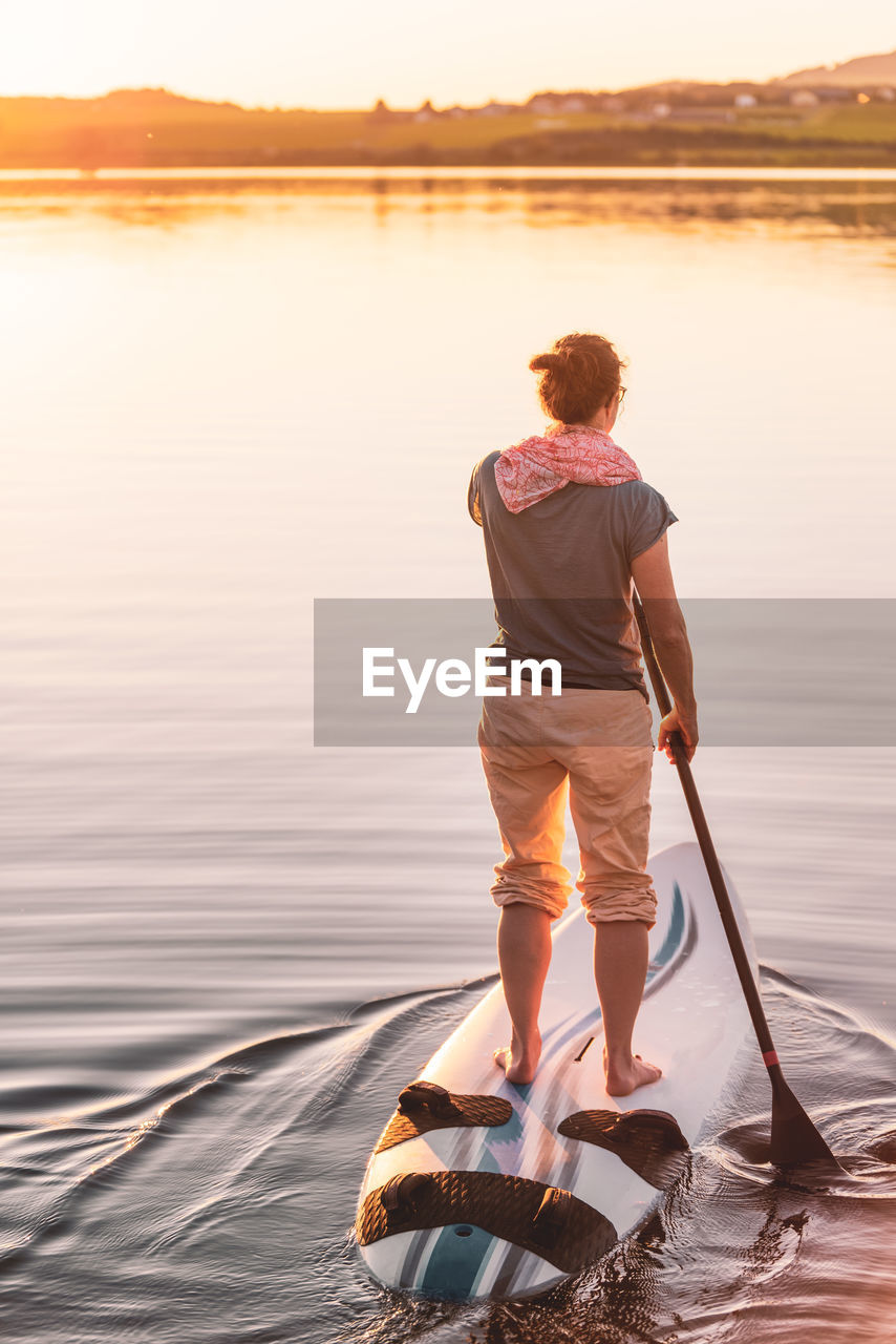 Young woman stand up paddling sup at sunset, lake wallersee, austria