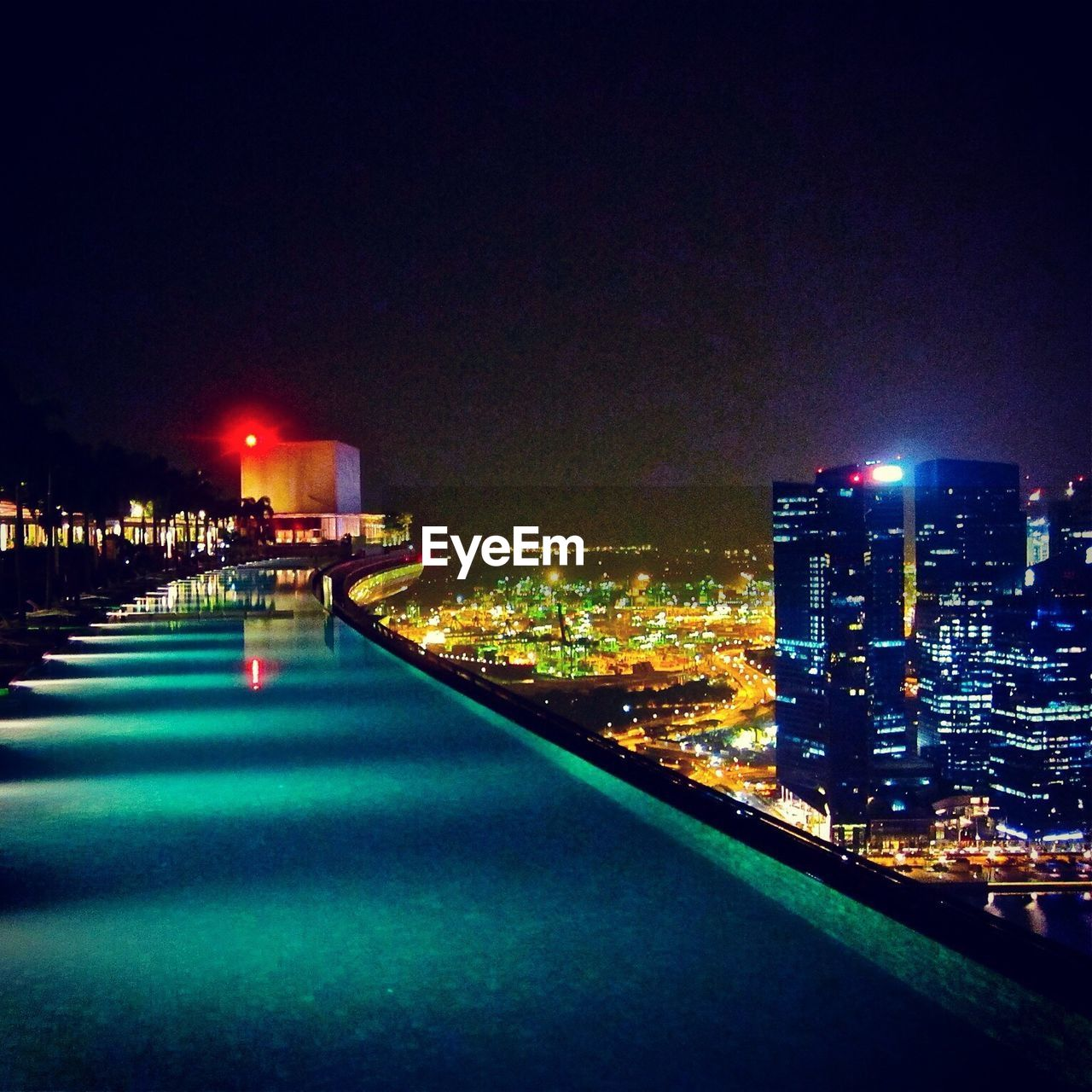 Illuminated Cityscape Against Clear Sky Seen From Infinity Pool Of Marina Bay Sands