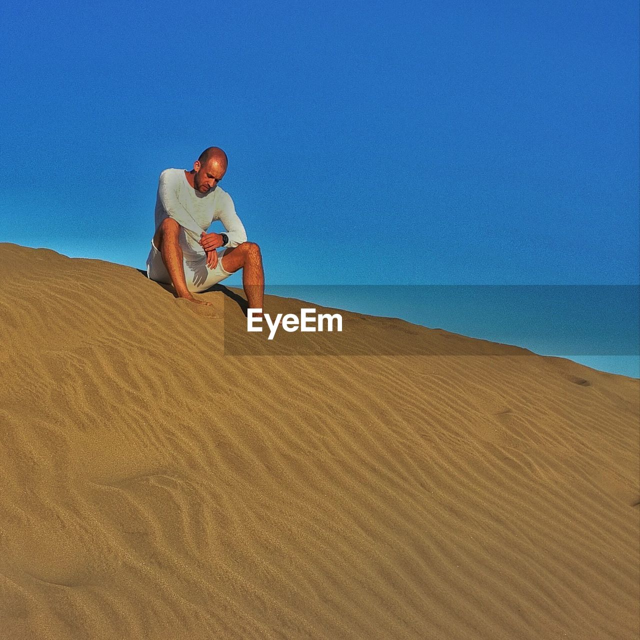Low Angle View Of Tired Man Sitting On Sand Dune Against Clear Blue Sky
