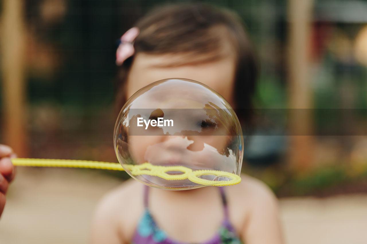 Close-Up Of Girl Seen Through Bubble