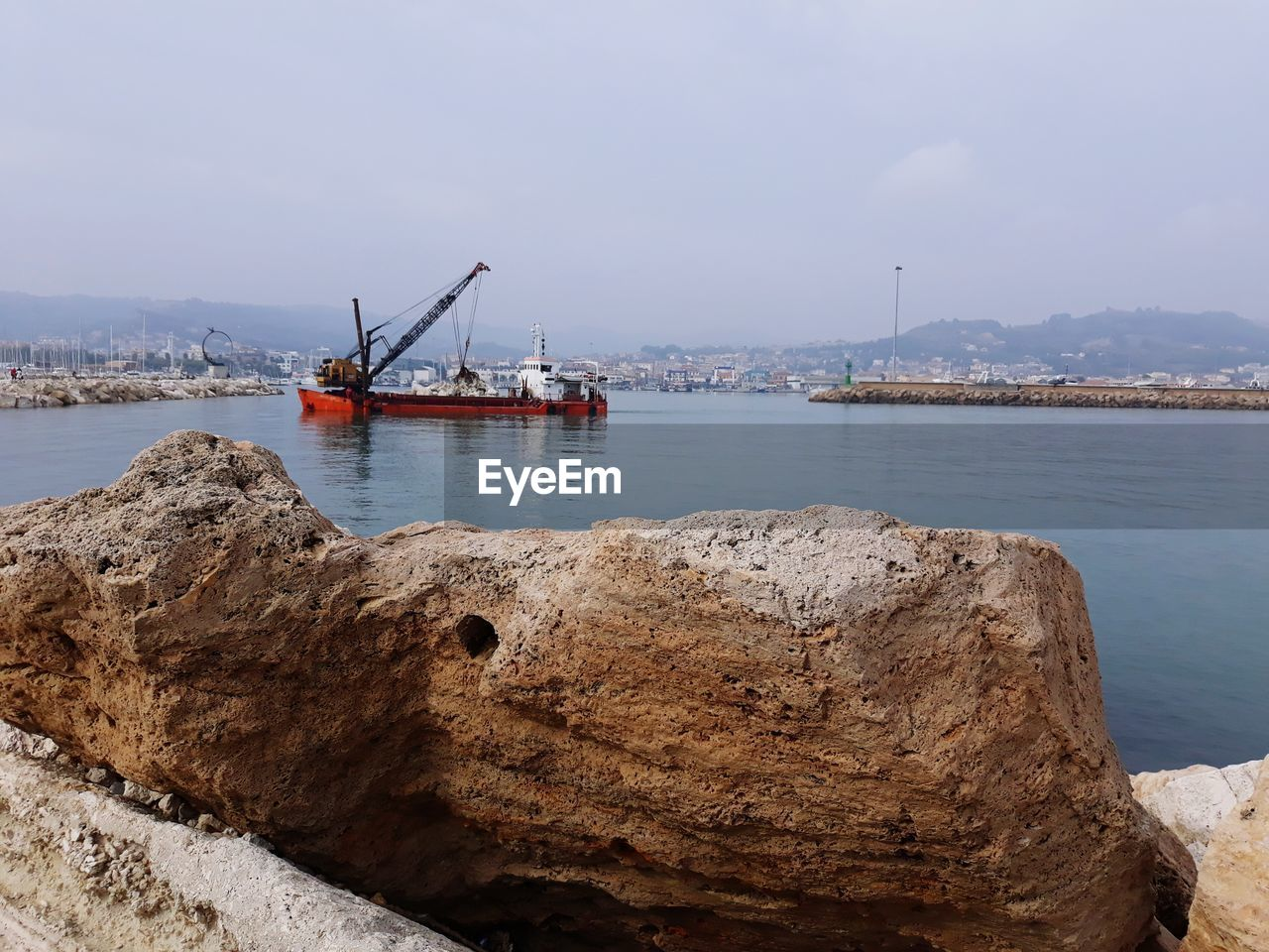 water, transportation, sea, rock, nautical vessel, sky, rock - object, solid, mode of transportation, nature, no people, day, tranquility, outdoors, harbor, tranquil scene, beauty in nature, industry, pier, construction equipment