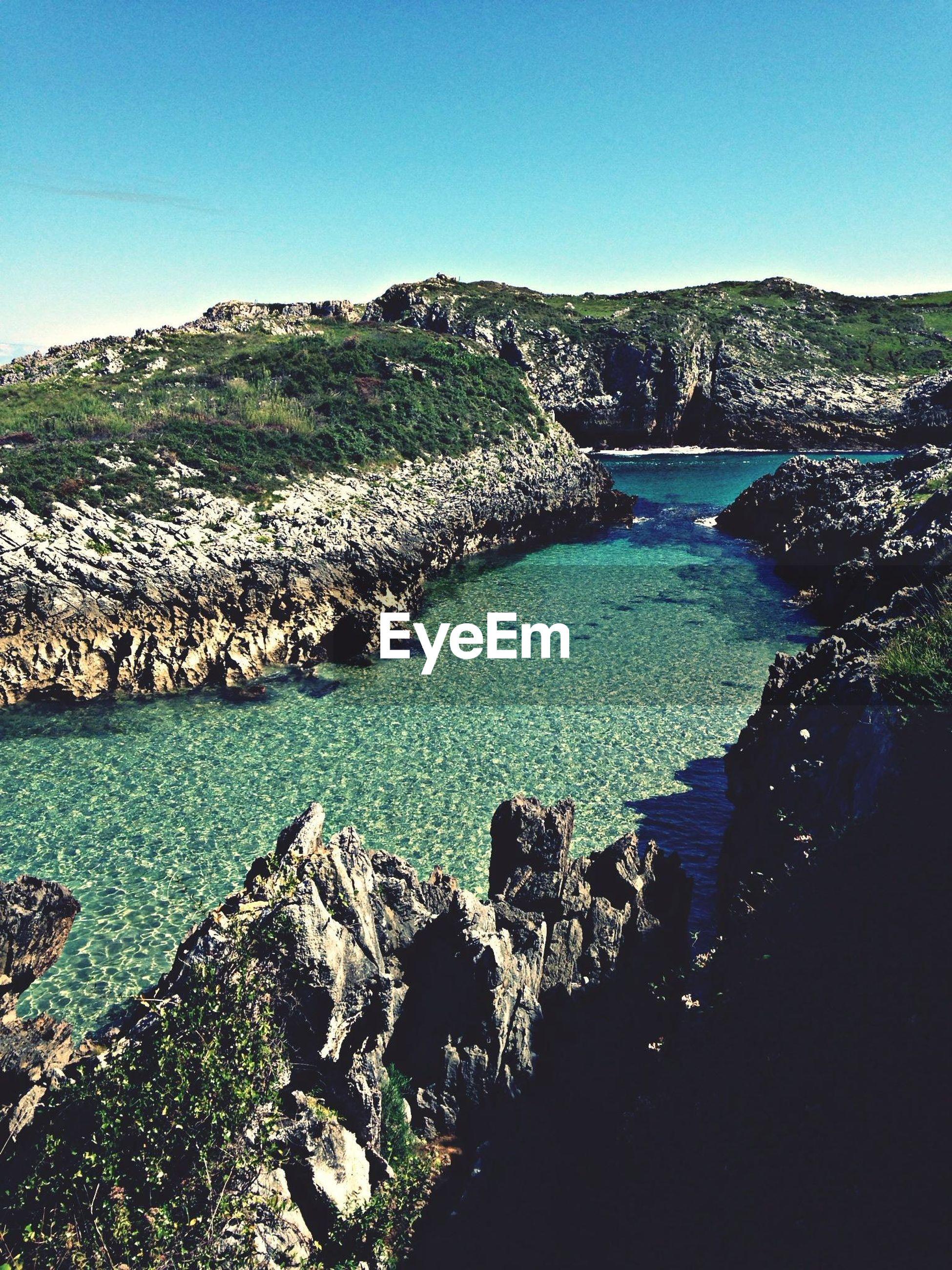 water, tranquil scene, tranquility, scenics, beauty in nature, clear sky, mountain, nature, blue, landscape, sea, idyllic, non-urban scene, rock - object, sky, sunlight, coastline, beach, remote, day