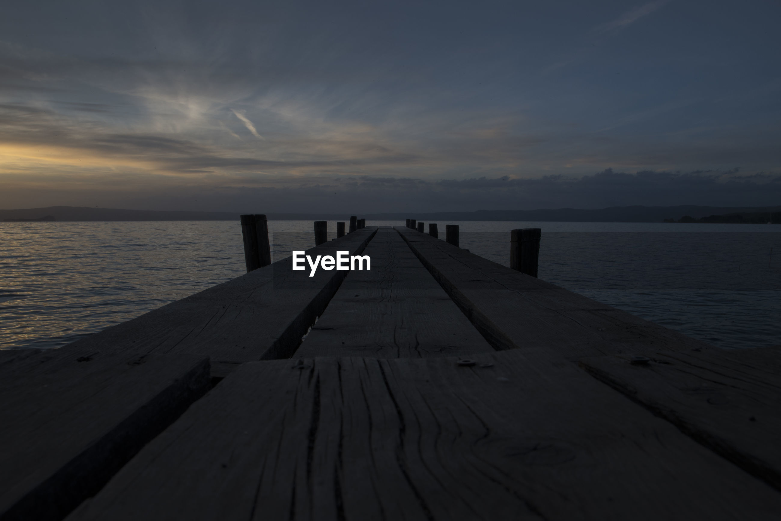 WOODEN JETTY ON PIER AT SEA AGAINST SKY