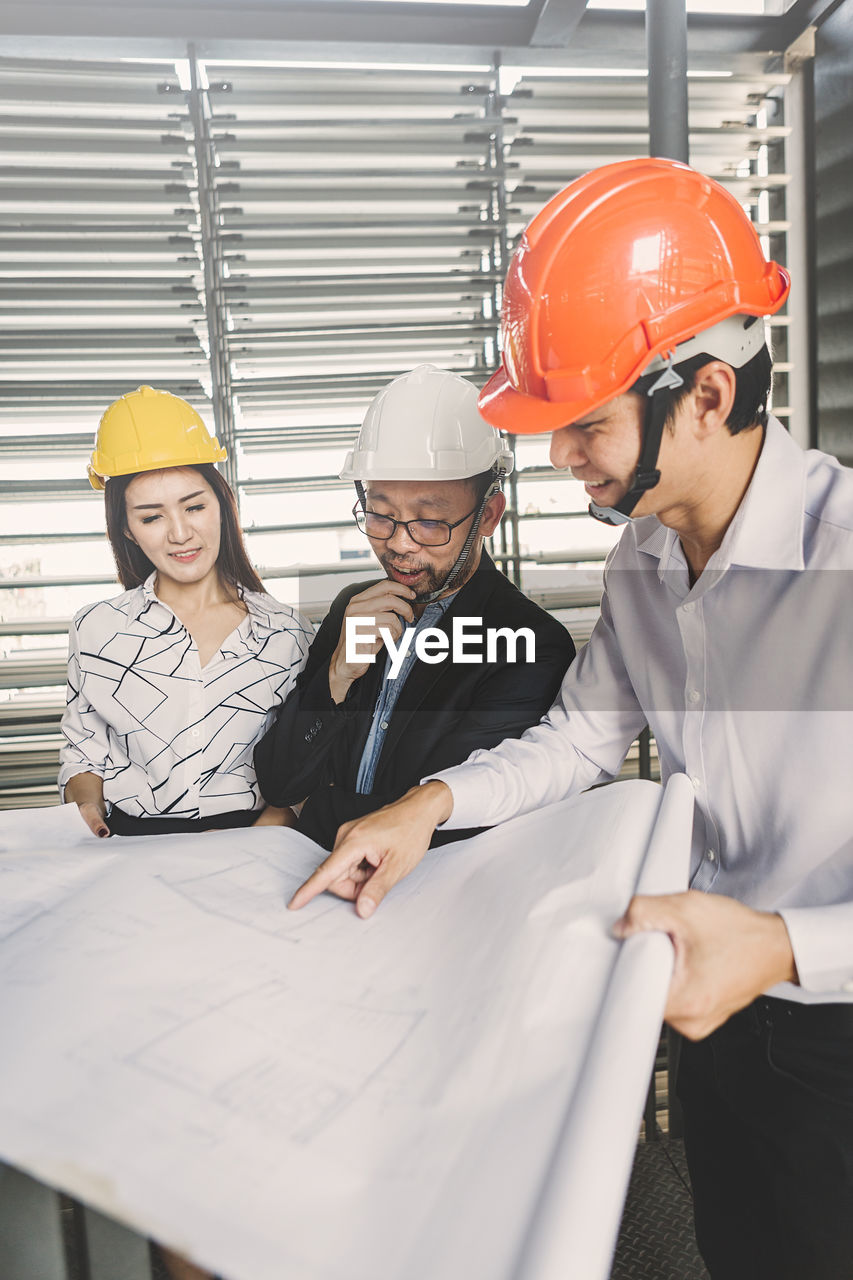 helmet, headwear, hardhat, hat, occupation, group of people, men, adult, working, protection, business, males, women, indoors, mature adult, protective workwear, coworker, safety, teamwork, blueprint, design professional, mature men, architect