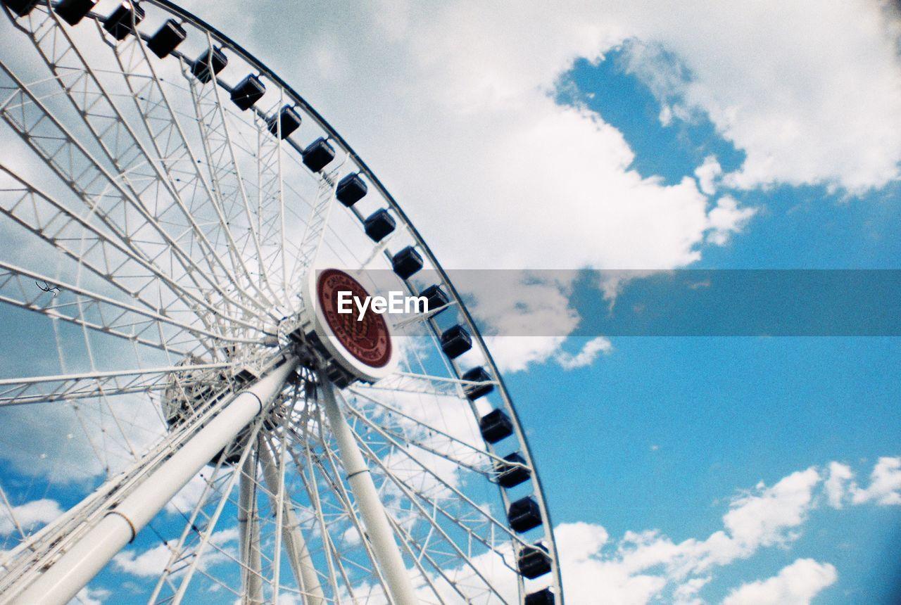 amusement park, amusement park ride, ferris wheel, sky, cloud - sky, arts culture and entertainment, leisure activity, fairground, low angle view, day, no people, nature, large, outdoors, circle, geometric shape, shape, carnival, fun, blue, wheel, spoke