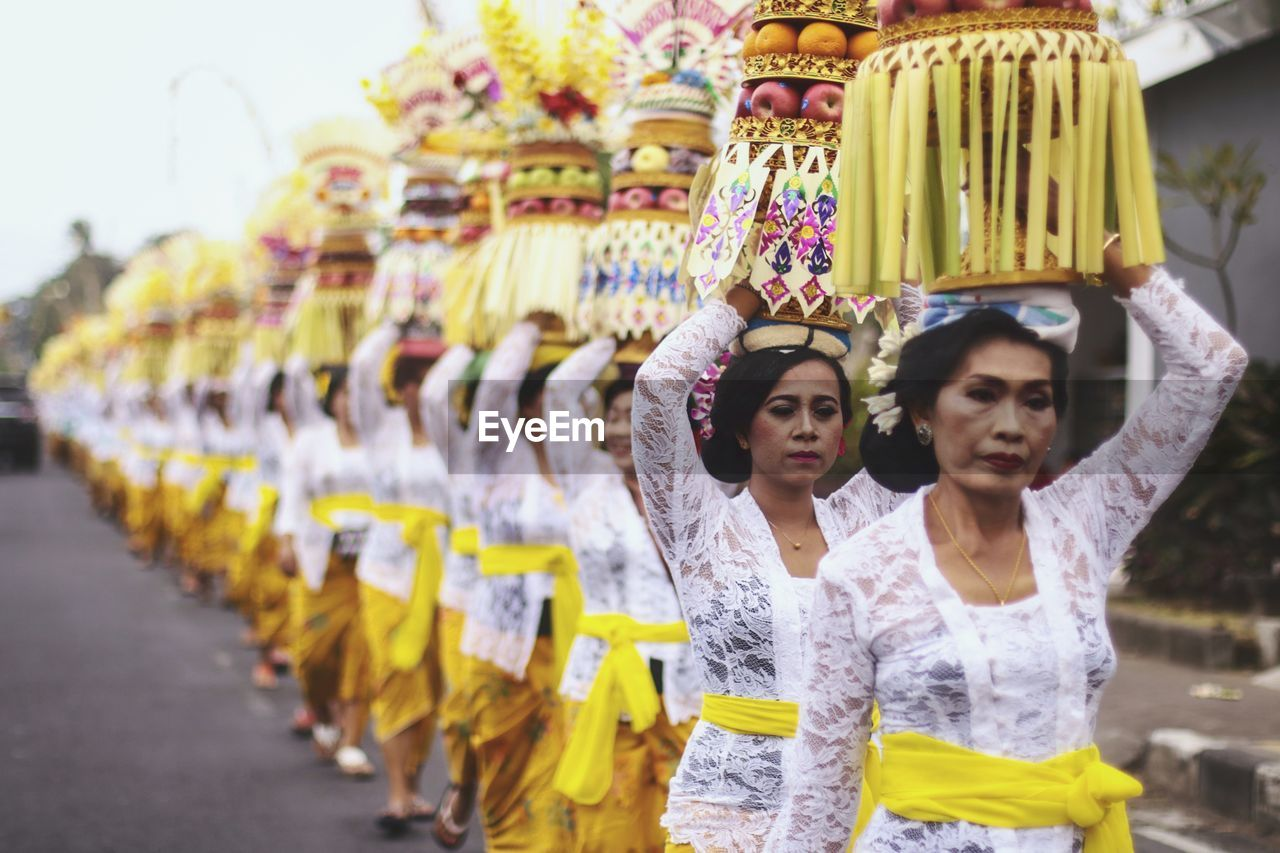 women, front view, real people, clothing, adult, young women, young adult, in a row, yellow, people, two people, lifestyles, traditional clothing, standing, casual clothing, looking, side by side, focus on foreground