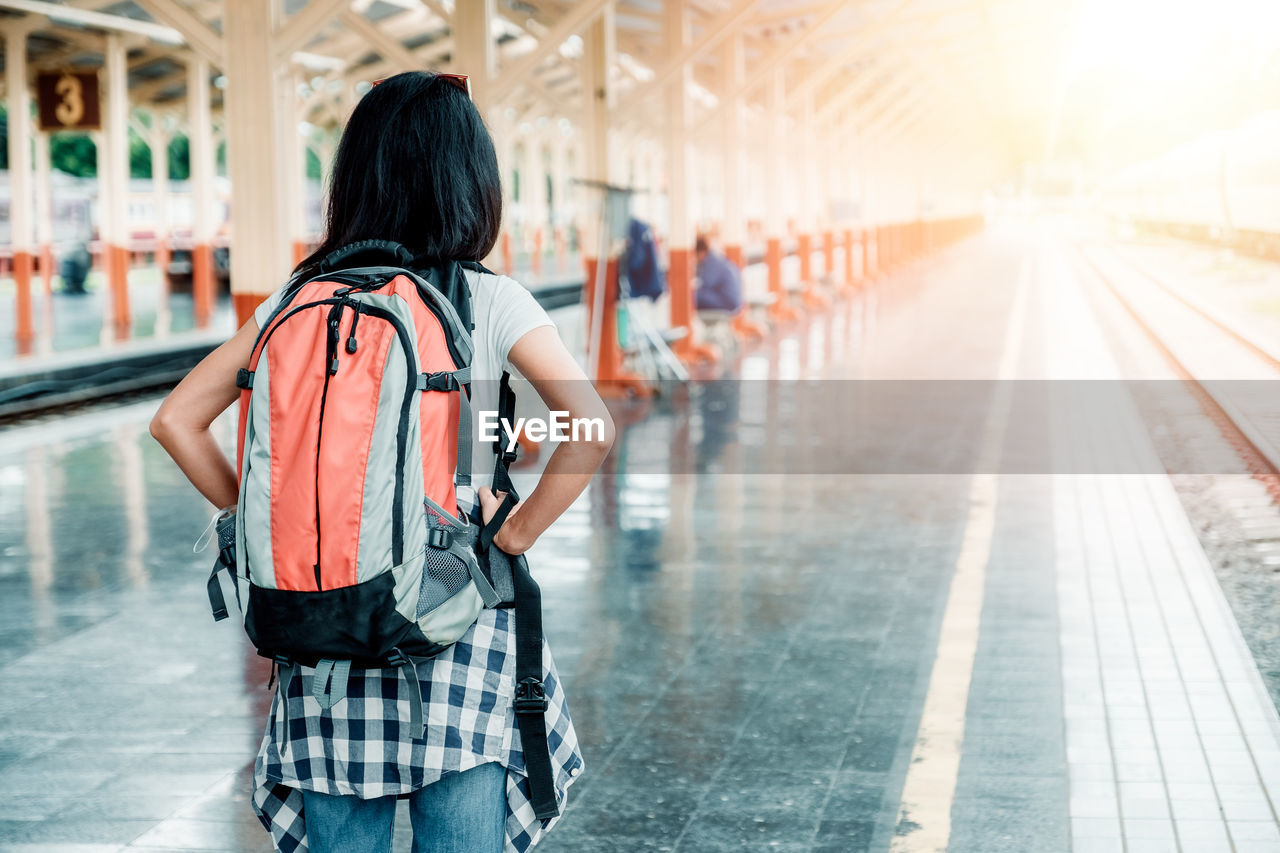 rear view, one person, real people, backpack, bag, lifestyles, adult, focus on foreground, women, casual clothing, three quarter length, transportation, walking, travel, standing, architecture, leisure activity, city, incidental people, hairstyle