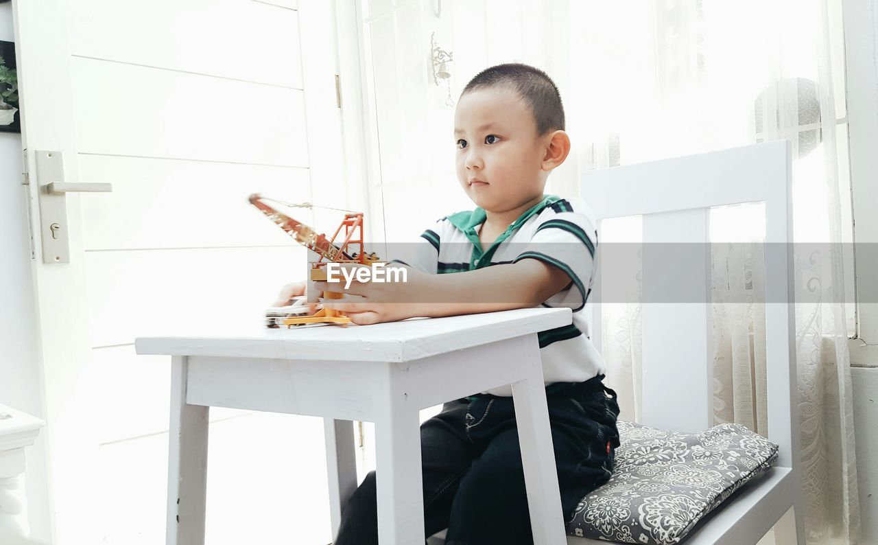 Boy Playing With Toy While Sitting On Chair