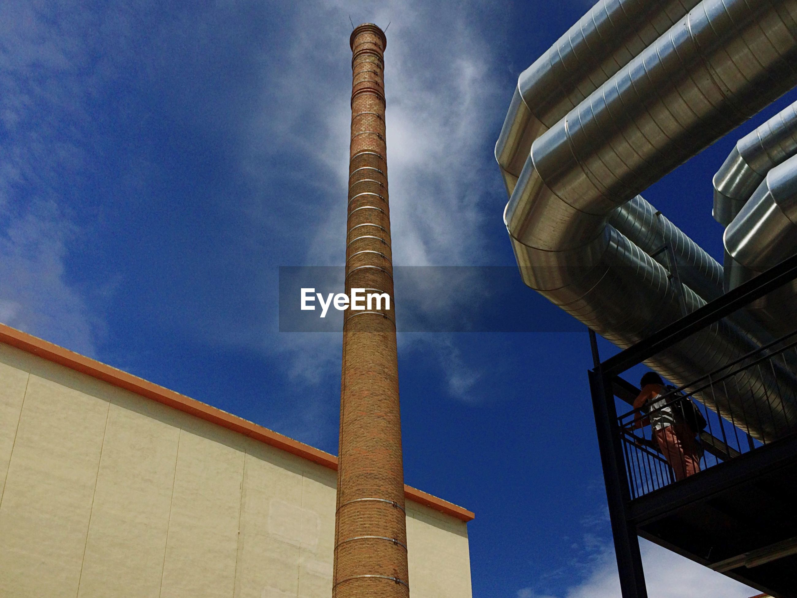 Low angle view of smoke stack and pipelines at industry against sky
