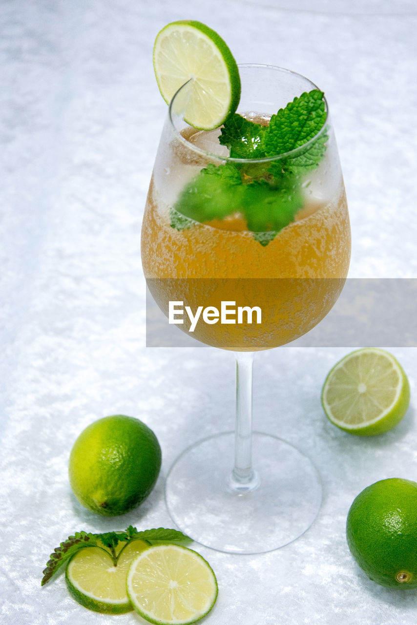 citrus fruit, drink, glass, fruit, alcohol, food and drink, refreshment, freshness, cocktail, drinking glass, slice, lemon, food, lime, household equipment, cold temperature, still life, close-up, no people, healthy eating, herb, mint leaf - culinary, garnish, tropical drink