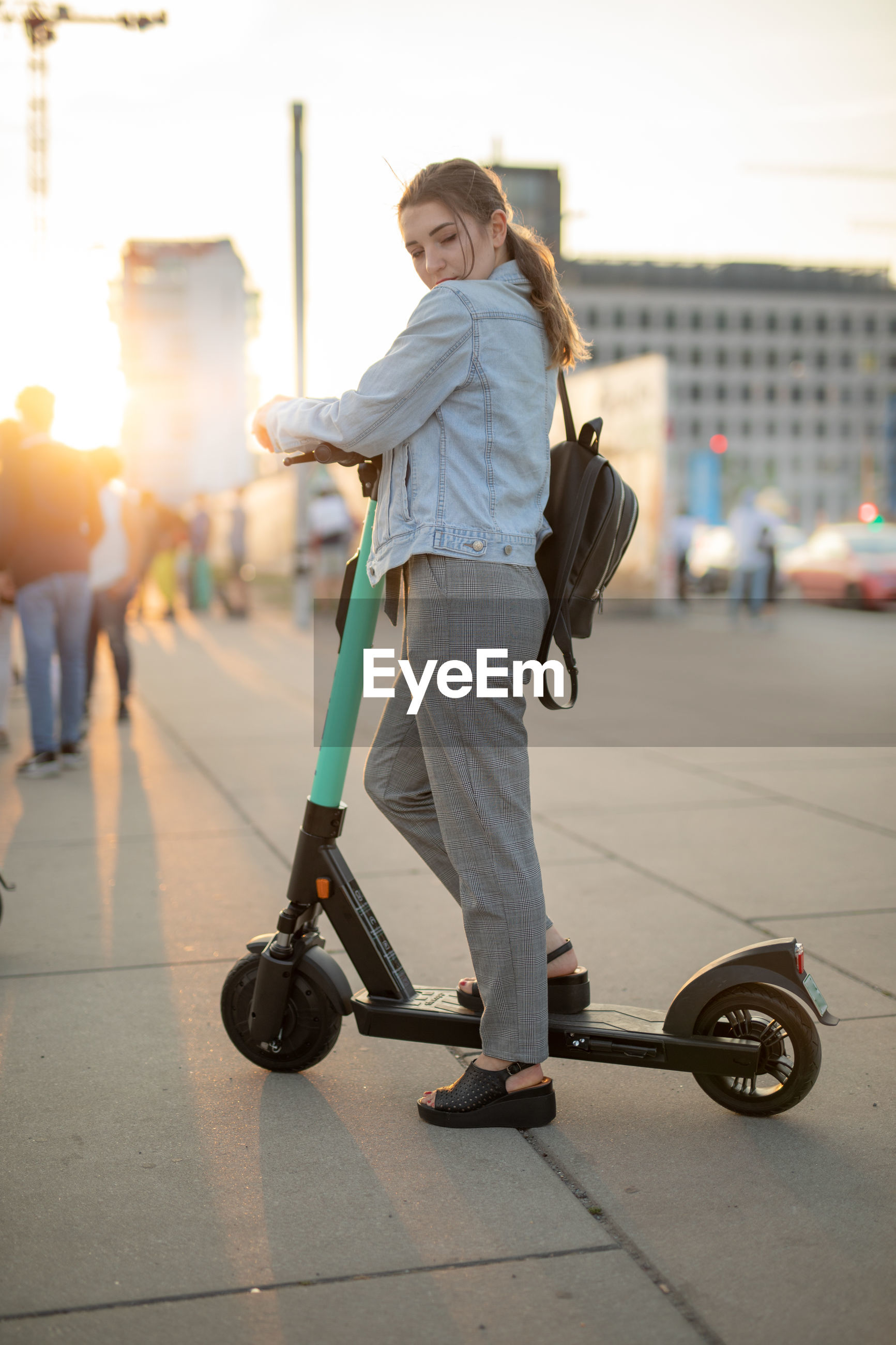 Young woman looking away while standing on push scooter against sky in city