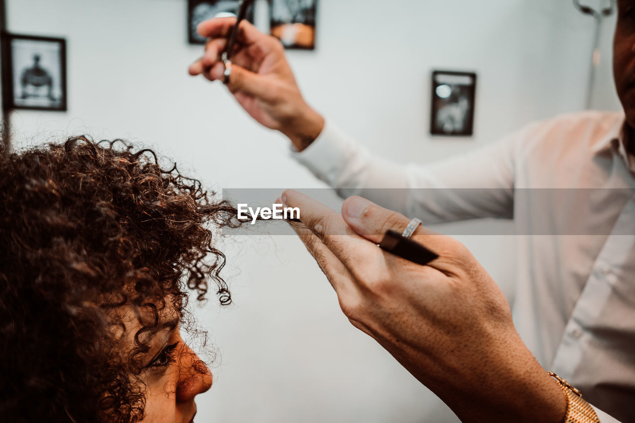 Midsection of barber cutting woman hair in salon