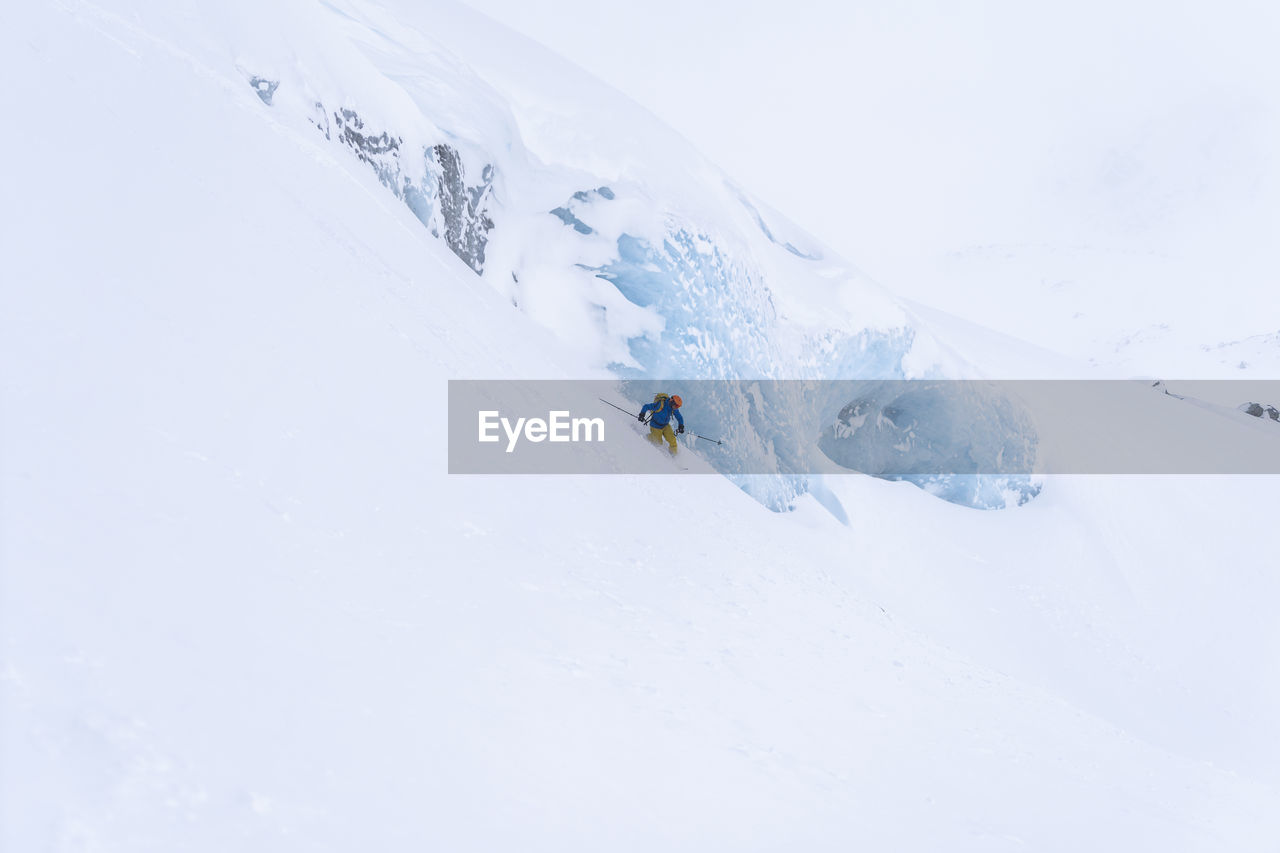Person skiing on snowcapped mountain