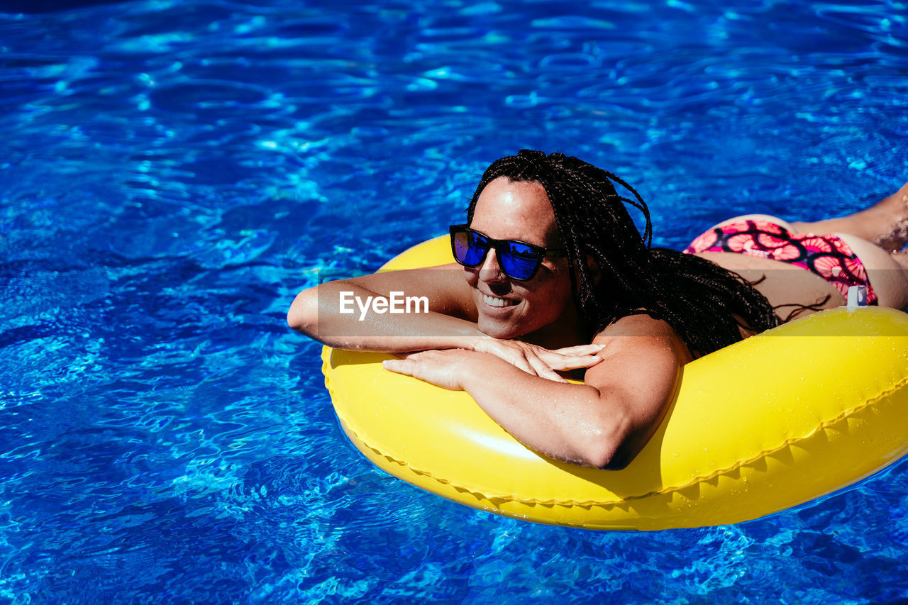 High angle portrait of young woman swimming in pool