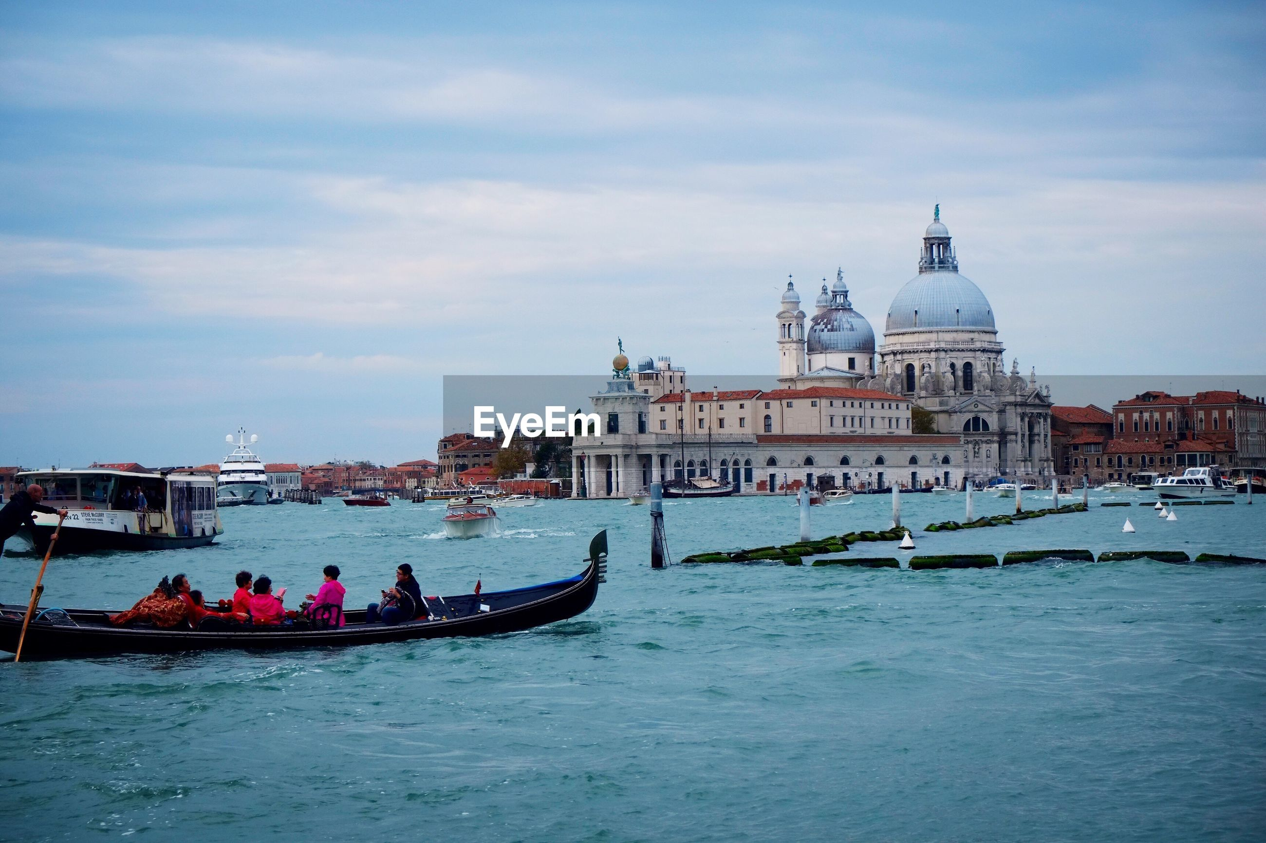 People in gondola on river against santa maria della salute