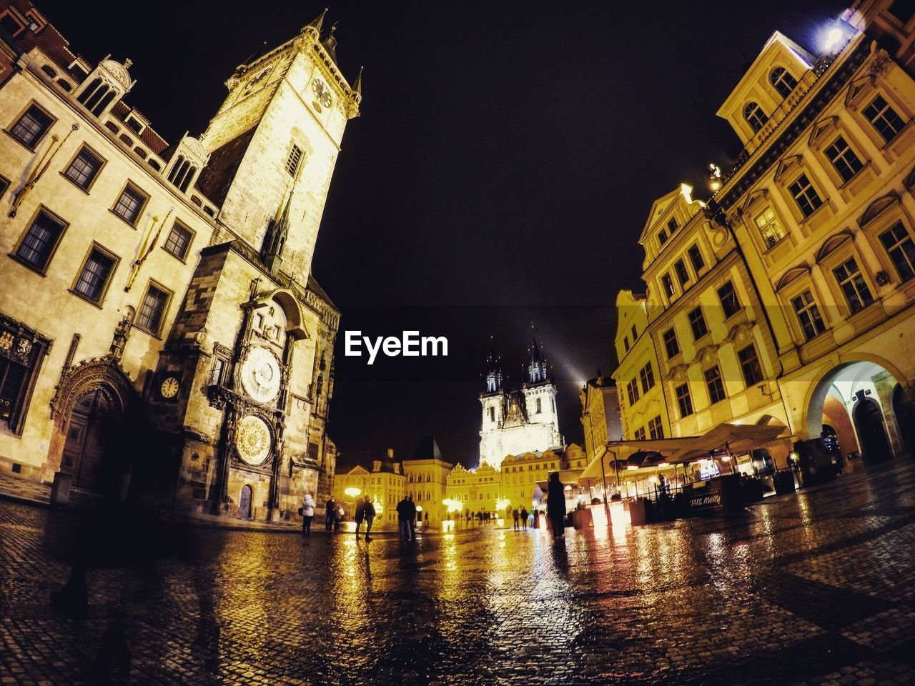 building exterior, architecture, built structure, night, large group of people, illuminated, place of worship, religion, town square, spirituality, history, men, real people, wet, travel destinations, outdoors, clock tower, city, water, sky, astronomical clock, people