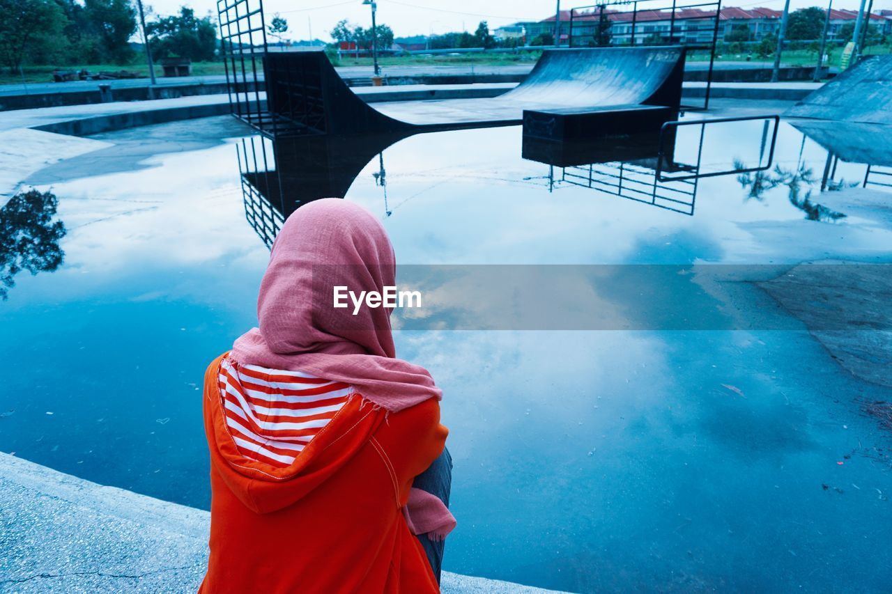 Rear View Of Woman Looking At Wet Skateboard Park During Sunset