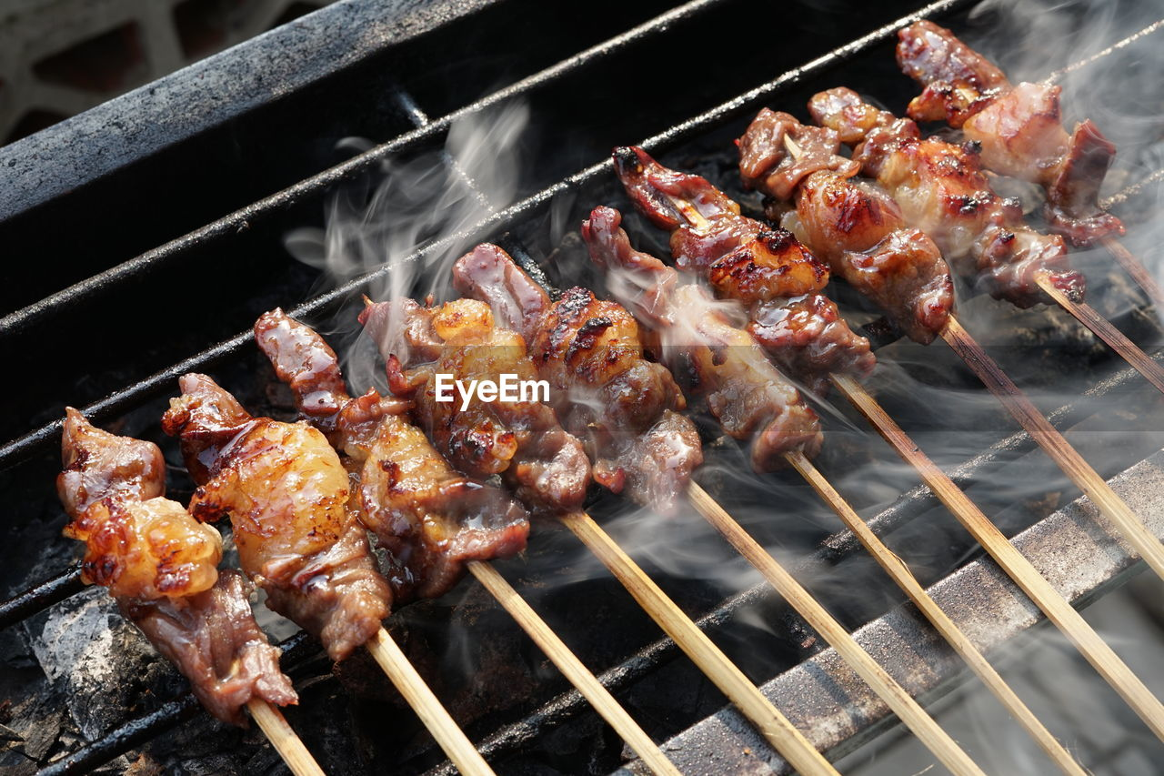 HIGH ANGLE VIEW OF MEAT COOKING ON BARBECUE